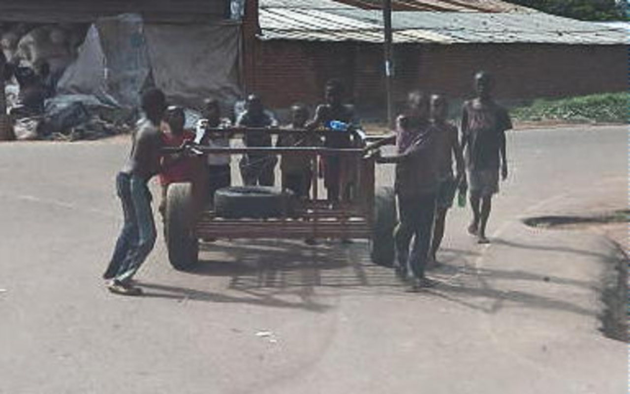 Guys pushing cart on street