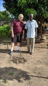 Planting an avocado tree outside the Mufumbwe hall