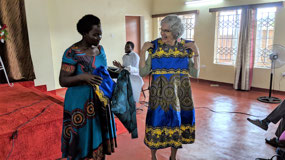 Jane Nhelma presenting dress to Bev