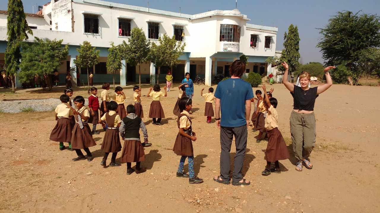 Jack and Kippy lead a game with school children.